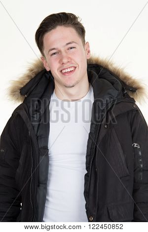 Portrait Close Up Of A Smiling Teenage Boy Wearing Winter Coat With Faux-fur.