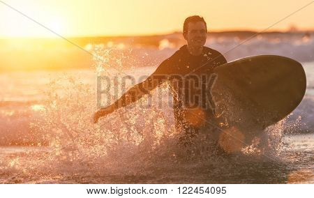 Surfer running out the water after long surfing