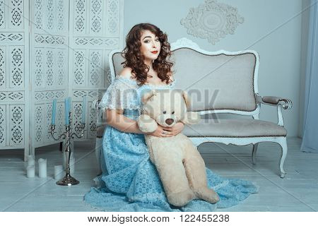 Plump woman with a toy bear sitting on the floor in the room.
