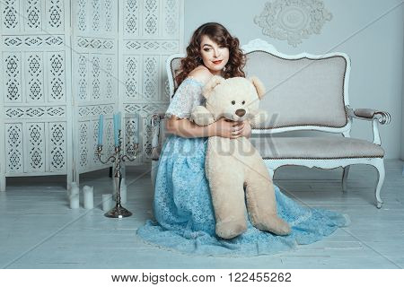 Plump woman hugging bear toy she sits on the floor in the room.