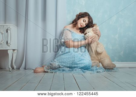 Plump woman sitting on the floor in the room she gently hugging bear toy.