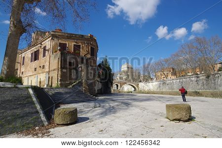 ROME, ITALY - MARCH 2, 2016: Photographer taking picture of Tiber Island with Fabricio bridge and the synagogue in the background