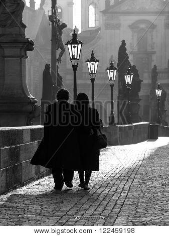 Couple walks on Charles Bridge in foggy morning, Prague, Czech Republic. Black and white image.