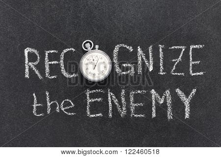 recognize the enemy phrase handwritten on chalkboard with vintage precise stopwatch used instead of O