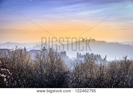 colorful romantic sunset in Langhe hills with fog and houses far away