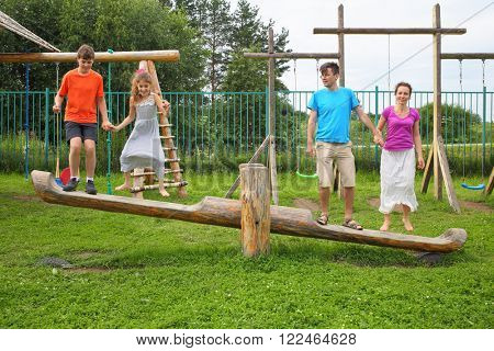Parents with son and daughter happy jumping on a swing on a wooden playground