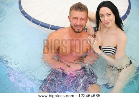 Portrait of a tanned man and light-skinned woman in pool at the aquapark