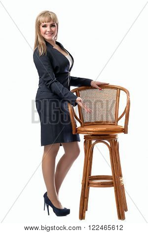 Young beautiful business woman inviting to sit on a chair. White isolated background