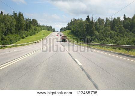 A road with moving cars and green surroundings on the sides
