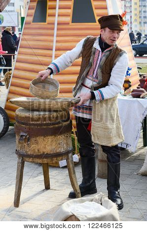 GOMEL BELARUS - MARCH 12 2016: Man is showing the work of old hand-mill during a Shrovetide entertainment outdoor