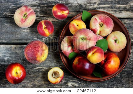 Summer fruit apricots peaches and nectarines on the wooden background