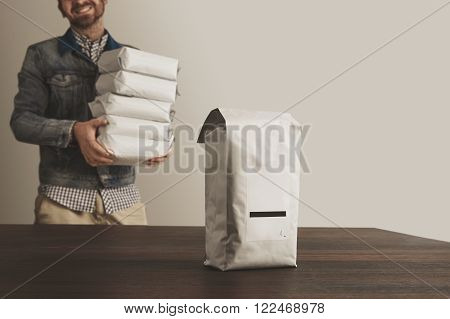 Big blank bulky sealed package with product isolated on wooden table in front of unfocused smiling man loader carrying other packages for shipping delivery sale. Small business artisan concept.