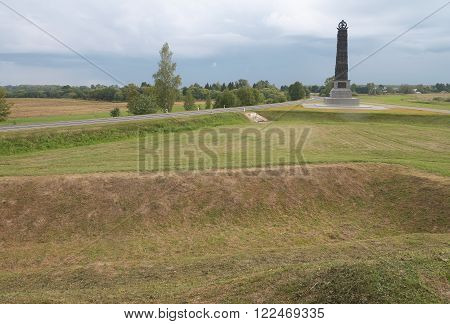 Commemorative monument at Borodino battle field in Russia and view on redoubt