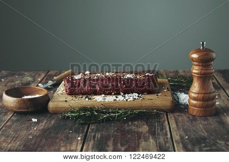Salted peppered piece of meat ready to grill on wooden table between herbs and spices on wooden vintage table side view
