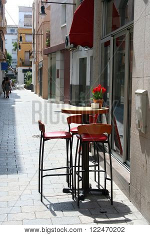 Small cute cafe for threesome in downtown street in oldtown Blanes, Catalonia, Spain