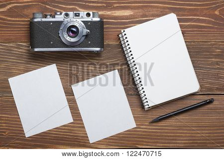 Travel, vacation concept. Camera, notepad, pen and photography on office wooden desk table. Top view with copy space for text.