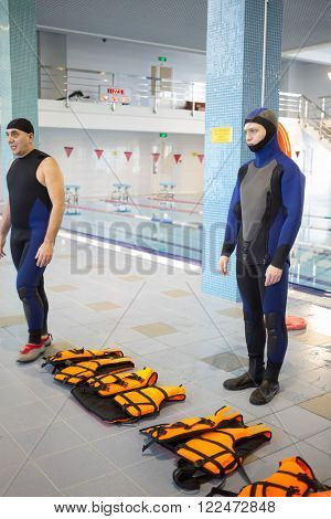 RUSSIA, MOSCOW - 10 DEC, 2014: Two divers are standing near orange life jackets at the pool in Training center for civil defense and emergency situations of Moscow.