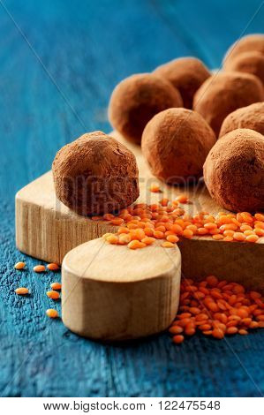 Homemade vegan truffles made with lentils and raw lentils on wooden board vertical