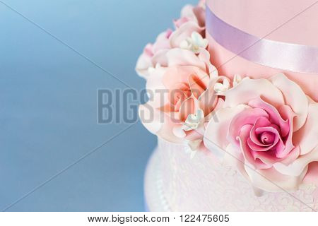 Cake decorated with roses on a blue background
