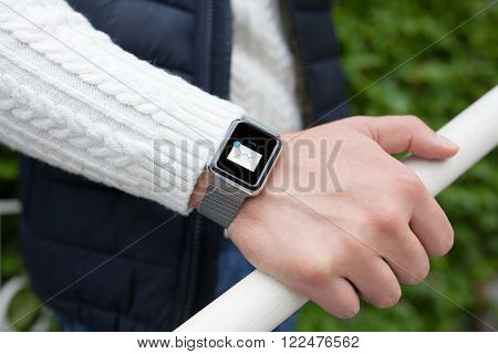 man hand and smart watch with mail in the screen on the street