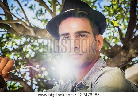 Handsome young man against olive tree branches, looking away, with sun flare next to his face, in a sunny day, wearing fedora hat