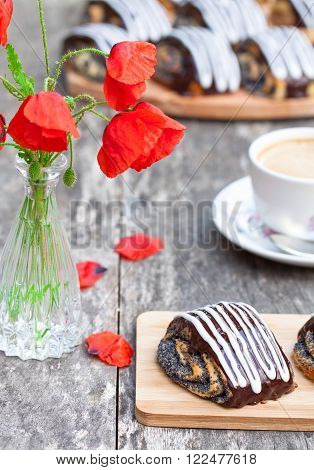 cup of coffee with poppy buns glazed with chocolate and poppy flowers ** Note: Shallow depth of field