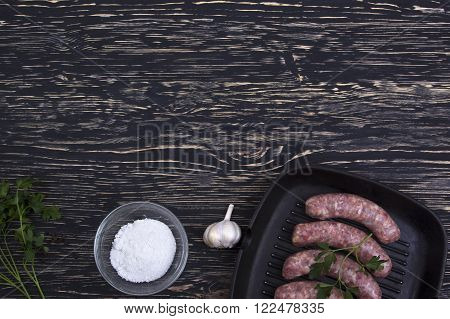 raw beef sausage in a frying pan with garlic on a wooden background, rustic