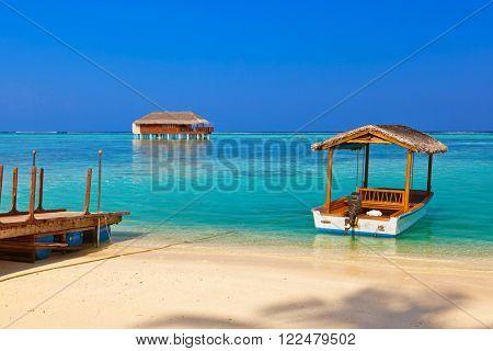 Boat and bungalow on Maldives island - nature travel background