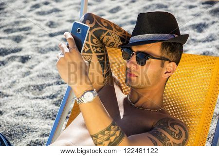 Young handsome man on beach sitting on deckchair while taking selfie photo with cell phone. Seascape with hills on background