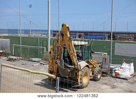 BARCELONA, SPAIN - JULY 31, 2015: Four wheeled excavator near a football field in Barcelona