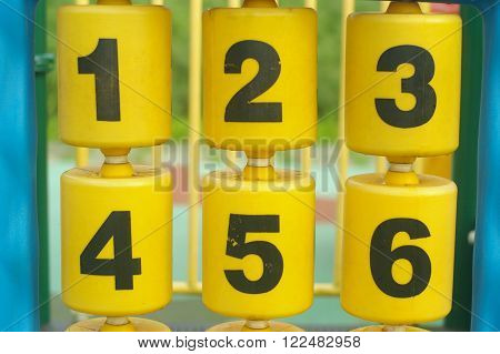 Numbers from one to six on yellow cylinders of a multi play system