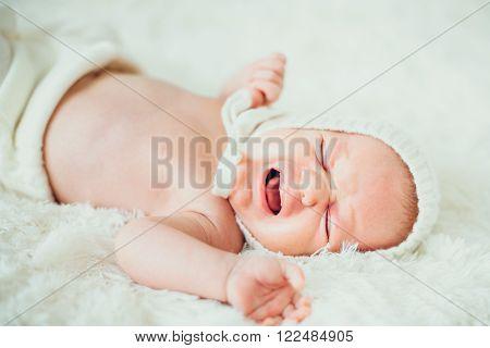 funny portrait dreamy little baby (child kidd infant) cry lying in a carpet. newborn. son. boy.