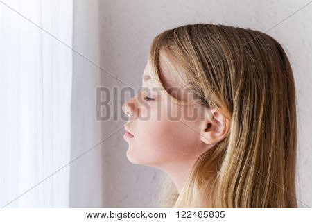 Caucasian Girl With Closed Eyes Near A Window