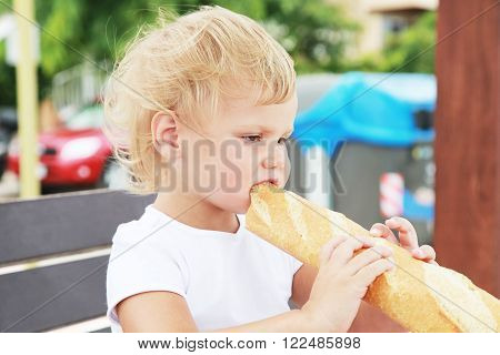 Caucasian Blond Baby Girl Eating French Baguette
