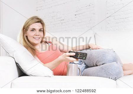 young attractive and blond hair woman smiling happy holding television remote controller watching TV sitting on sofa couch at home living room relaxed in lifestyle concept