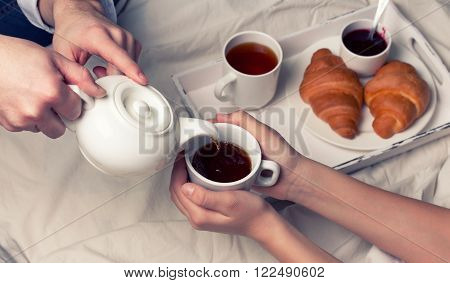 breakfast in bed with tea, croissants and strawberry jam