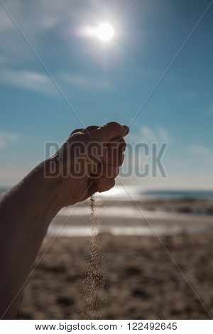 Sand falling from the woman's hand against the sea
