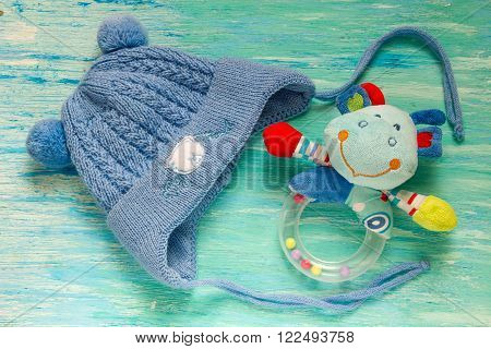 baby shower baby hat with ears knitted pixie hat boy announcement blue on wooden background children's room the pile accessories on table Mother care