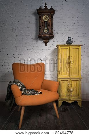 Composition of vintage orange armchair, yellow cupboard, pendulum clock and black scarf