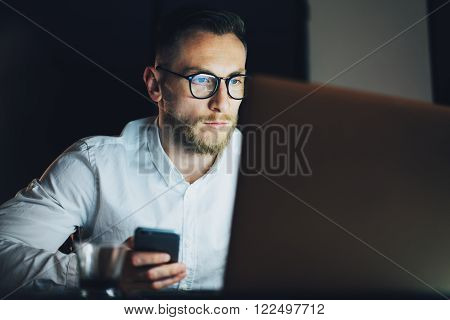 Portrait bearded businessman working on modern loft office at night. Man using contemporary smartphone, blurred background.