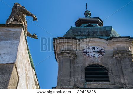 Statue of a saint and a tower with clocks. Church of Saint Cross in Devin Bratislava Slovakia.