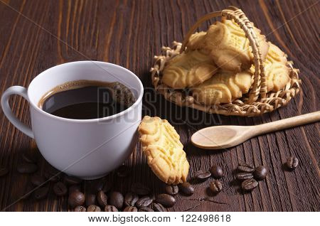 Cup of hot coffee and shortbread cookies on brown wooden table