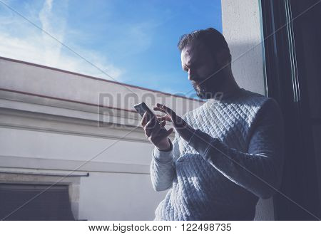 Portrait bearded man in modern loft. Man using contemporary smartphone, blue sky background. Horizontal