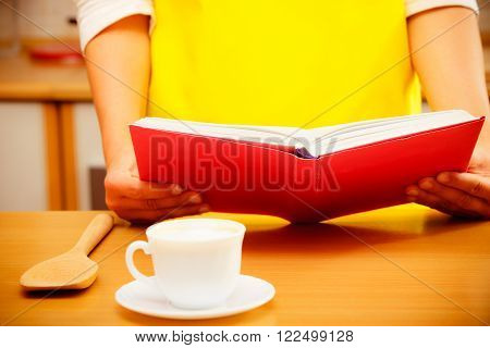 Housewife Woman Reading Cookbook In Kitchen.