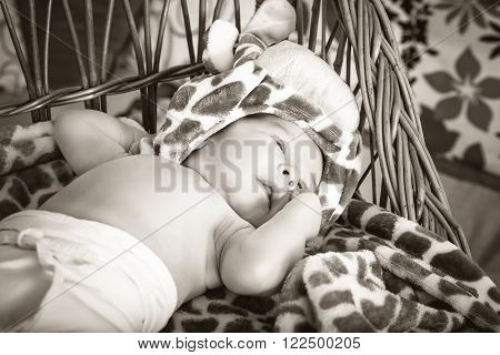 Portrait Of Beautiful Boy Lying In Wicker Basket