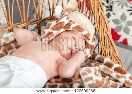 Portrait Of Beautiful Boy Lying In Wicker Basket