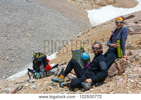 Young Man and Woman Traveling Outdoor Relaxing on Rocky Moraine with Backpacks and Thermoses Drinking Refreshments Fun Pleasure Casual Sporty Style Clothing