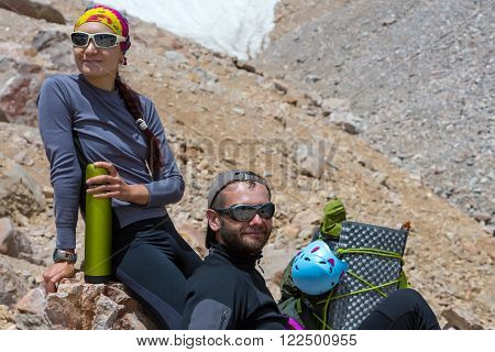 Young Man and Woman Traveling Outdoor Relaxing on Rocky Moraine with Backpacks Thermos Gear Helmet Drinking Refreshments Fun Pleasure Casual Sporty Style Clothing