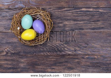 Three Easter colorful eggs in bird nest on wooden background