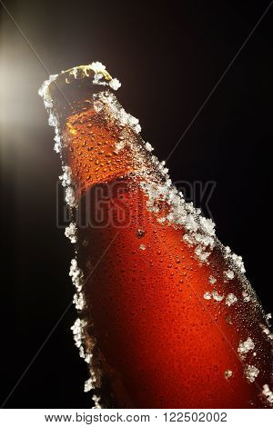 Cold brown bottle of beer with water droplets ice and light beam on top over black background